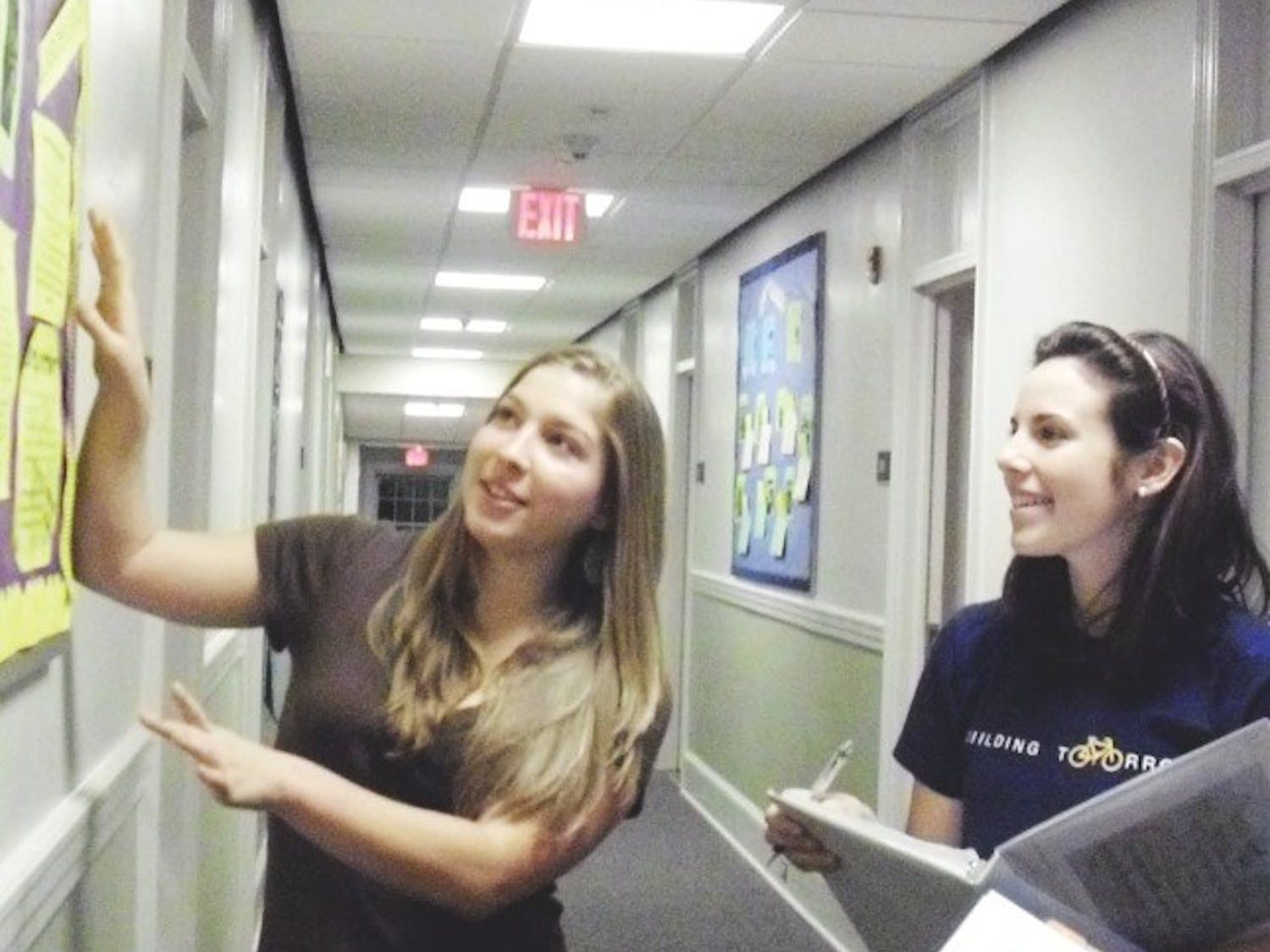 Natassia Rodriguz, a Residential Advisor, talks to Alexandra Lucas and other residents in the W.E.L.L. community of McIver Residence Hall.