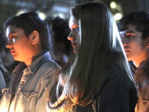Students gather on the steps of Wilson Library Friday to attend a vigil honoring the lost and threatened lives in the transgender community.