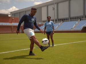 Hassan Pinto, kicks a ball in the air with his foot at the new UNC Soccer Stadium as his daughter, Brianna Pinto watches on Wednesday, Aug. 21 2019.
