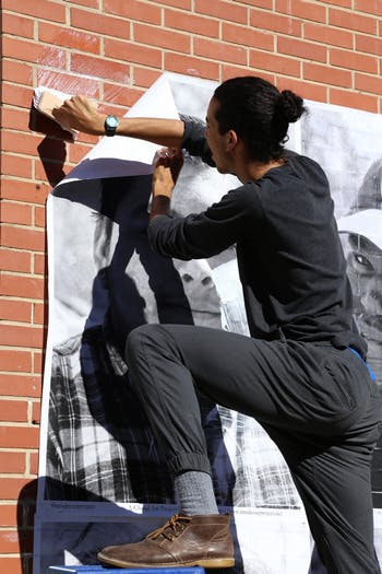 Junior Norman Archer (UNC) helps hang portraits of students on the walls of Phoenix Academy in an effort to knock down barriers surrounding identity.