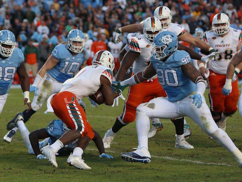 Former North Carolina defensive lineman Nazair Jones (90) tackles Miami running back Mark Walton (1) in 2015.