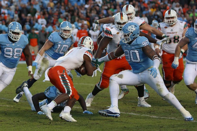 Former North Carolina defensive lineman Nazair Jones (90) tackles Miami running back Mark Walton (1) in 2015.