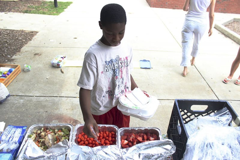 Anton Enoch serves himself food during Friday Fun Day, a free lunch event for families in the Chapel Hill area.