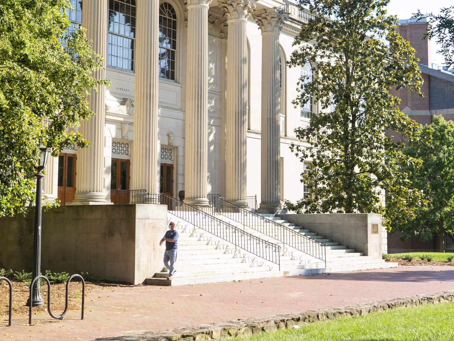 A summer facilities worker walks to the edge of Wilson Library while wearing a mask as a precautionary measure against COVID-19 on Sunday, June 7, 2020.