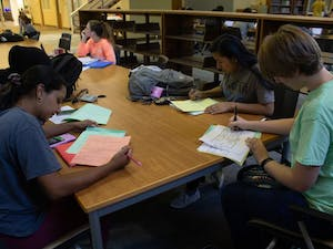UNC students Anna Monocha, Laurel Thomas, Marina Perez, and Wid Alsadoon work together on a group project before Fall Break in Davis Library on Thursday, Oct. 10, 2019.