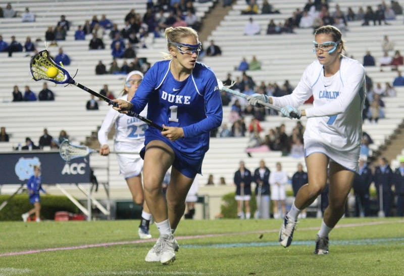 Women's lacrosse suffers a loss 7-6 to Duke in overtime on Wednesday in Kenan Stadium. Defender Margaret Corzel (9) attempts to block out an opponent.