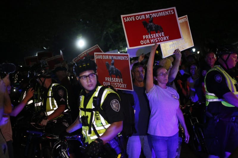 Police escort demonstrators out of McCorkle Place on Thursday night.