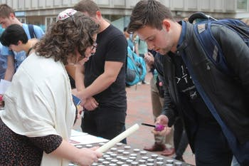 Rabbi Melissa B. Simon (left) helps Maximilian Jeremy Bazil, a sophomore biology major, (right) light a candle in honor of the victims of the Pittsburg synagogue shooting at the Hillel Stand Together Against Hate Solidarity Gathering in front of the Student Union on Thursday, Nov. 1, 2018.