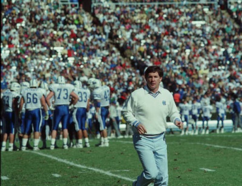 UNC Head Coach Mack Brown runs on the field during a game versus Duke in Kenan Memorial Stadium on Nov. 11, 1989. In the Hugh Morton Photographs and Films #P0081, copyright 1989, 1989, North Carolina Collection, University of North Carolina at Chapel Hill Library.