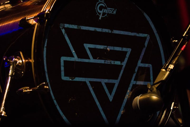 The band's drum set is adorned with their logo, which also served as the album cover for their first release.