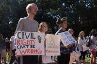 (From left to right) Riley Curtis, Reiley Baker, and Amy Estrada stand in the front of the crowd at South Building during the Believe Surivors Rally Friday, Oct. 12, 2018. Demonstrators gathered at South Building to hear testimonies and  proceed to march to fraternity court in support of survivors of sexual harrassment and assault.