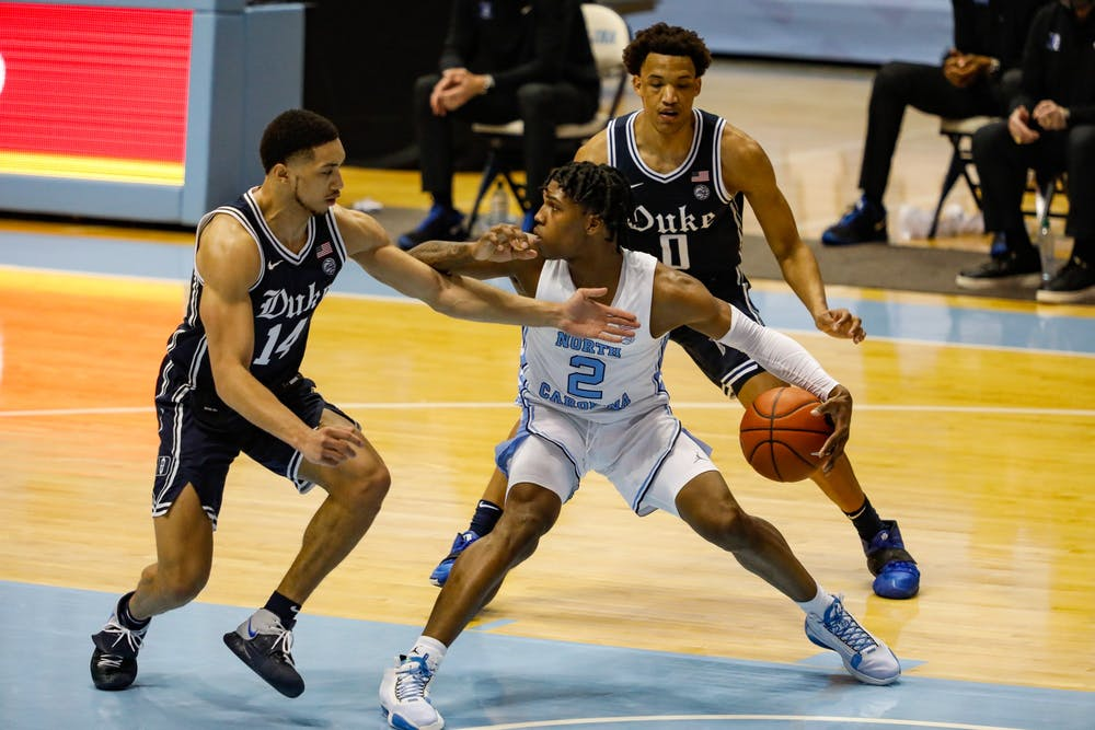 Duke senior guard Jordan Goldwire (14) and sophomore forward Wendell Moore Jr. (0) defend UNC freshman guard Caleb Love (2) in the Dean Dome on March 6, 2021. The Tar Heels beat the Blue Devils 91-73.