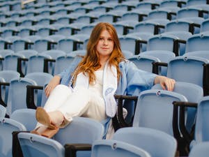 """Sophie Swift, a senior computer science major, poses for a portrait at Kenan Memorial Stadium on Wednesday, Apr. 28, 2021. """"I want to be true to myself,"""" says Swift, who's opting to wear a jumpsuit to the ceremony. """"And dress in a way that really feels like me."""""""