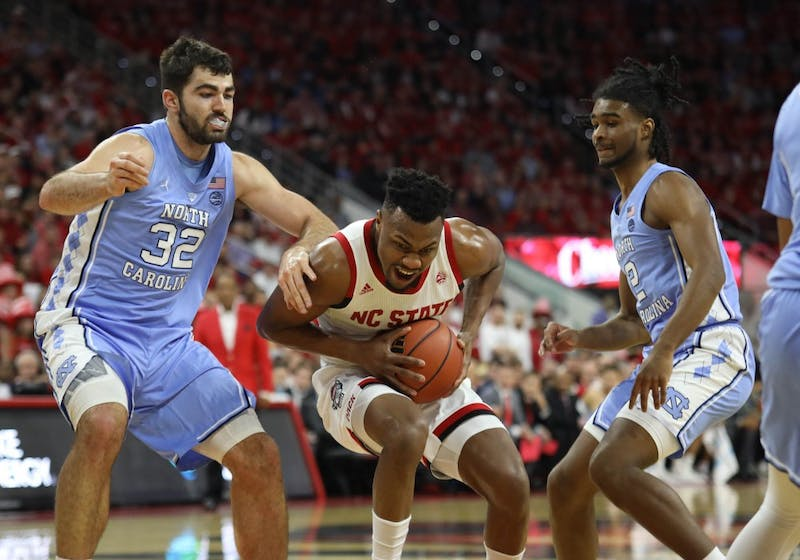 Forward Luke Maye (32) and guard Coby White (2) defend NC State guard Torin Dorn (2) in PNC Arena Tuesday, Jan. 8, 2019. UNC defeated NC State 90-82.