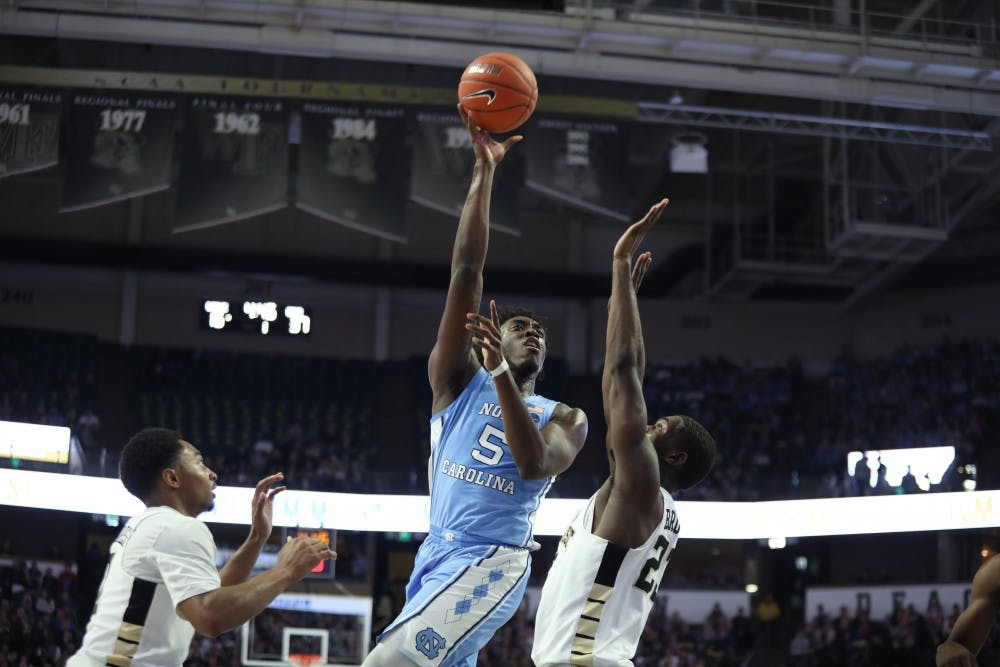 <p>Wake Forest sophomore guard Chaundee Brown (23) attempts to block UNC first-year forward Nassir Little (5) during No. 8 UNC's 95-57 win over Wake Forest on Saturday, Feb. 16, 2019 at Lawrence Joel Veterans Memorial Coliseum. &nbsp;&nbsp;&nbsp;</p>