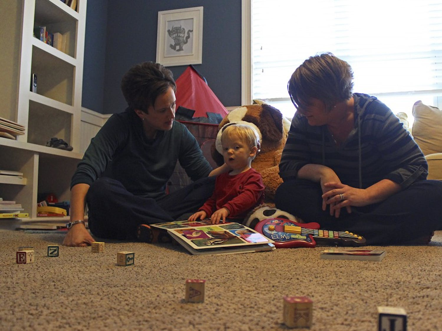 Jennifer Tharrington (left) and spouse Anna play with their son Jack, 18 months, in his play room in their home in Chapel Hill on Sunday, Feb. 15.