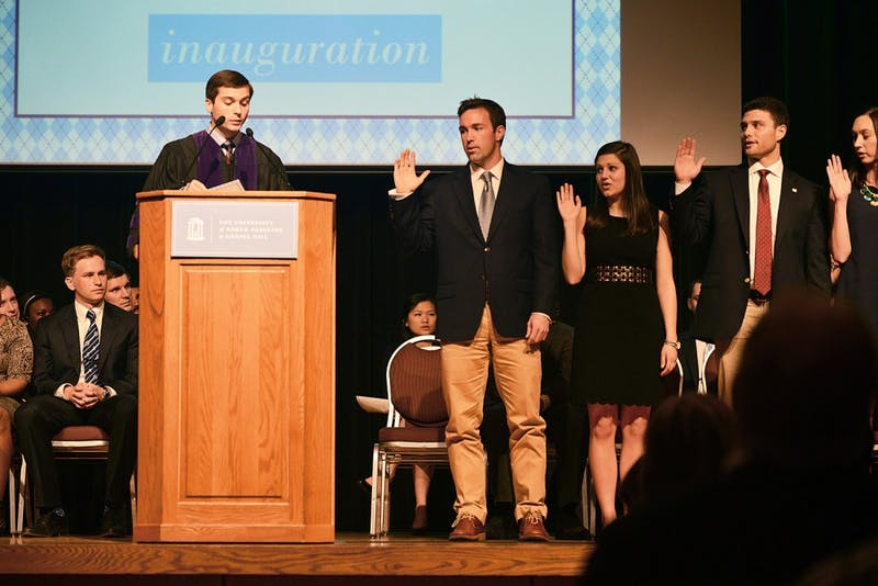 Junior Houston Summers takes his oath of office, becoming student body president for the 2015-16 academic year on Tuesday. Rachel Gogal (right) was sworn in as his vice president.