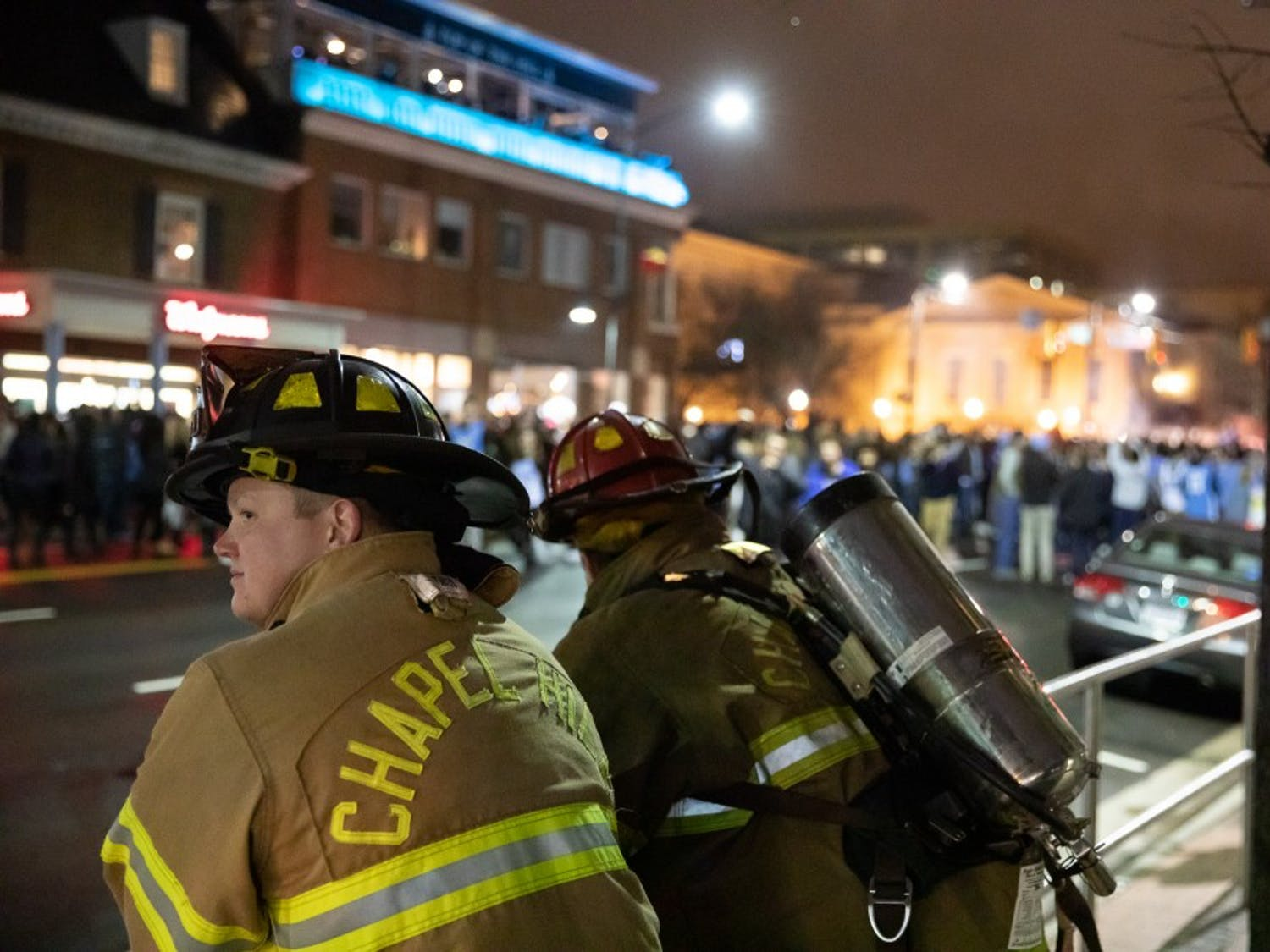 Chapel Hill firefighters monitor the rush to Franklin Street follwing  the Tar Heel's 88-72 win against the Duke Blue Devils on Wednesday, Feb. 20, 2019 in Chapel Hill, N.C. It is a yearly tradition for UNC students to run to the intersection of the Franklin Street and Columbia Street after a Tar Heel win against the Blue Devils.