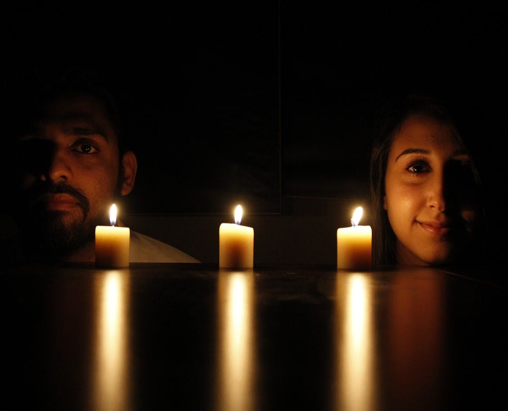 <p>Imad Ahmad (left), Deah's best friend and roommate, and Lina Chaarawi, Yusor and Razan's cousin, pose in front of candles for each of Our Three Winners.</p>