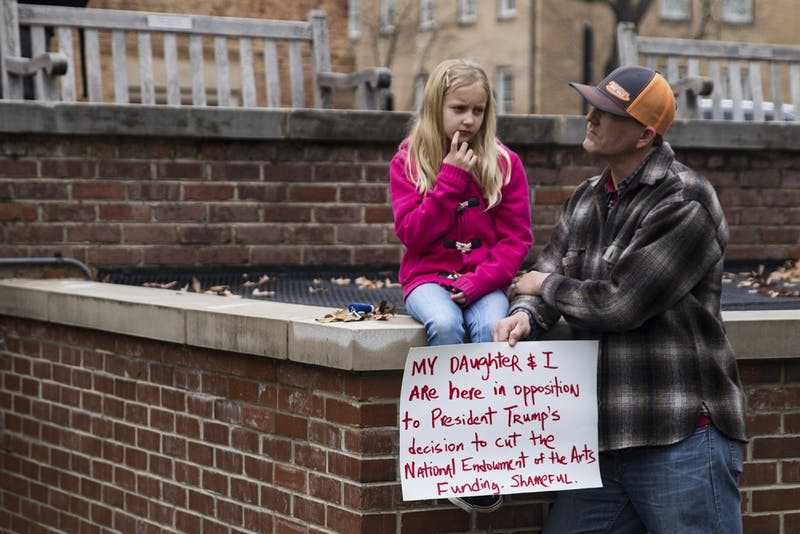 James Strong and his daughter, Avery, protest President Trump's decision cut tuning to the National Endowment of the Arts in January.