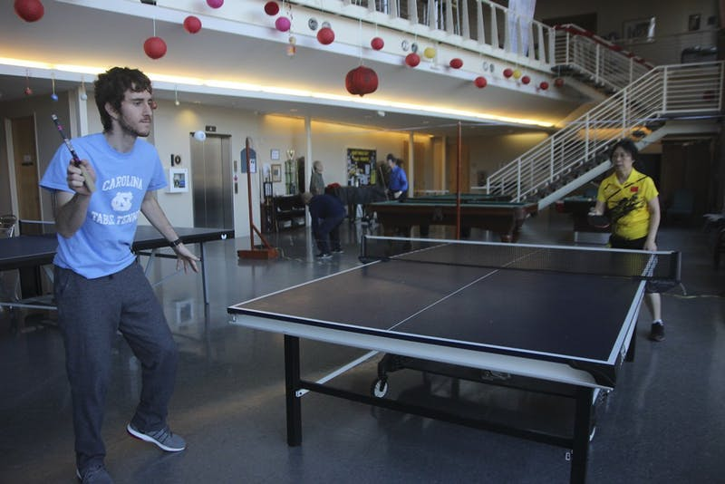 UNC sophomore and club table tennis member Abraham Post serves the ball to his opponent Wei Qu, a member of the senior citizen team.