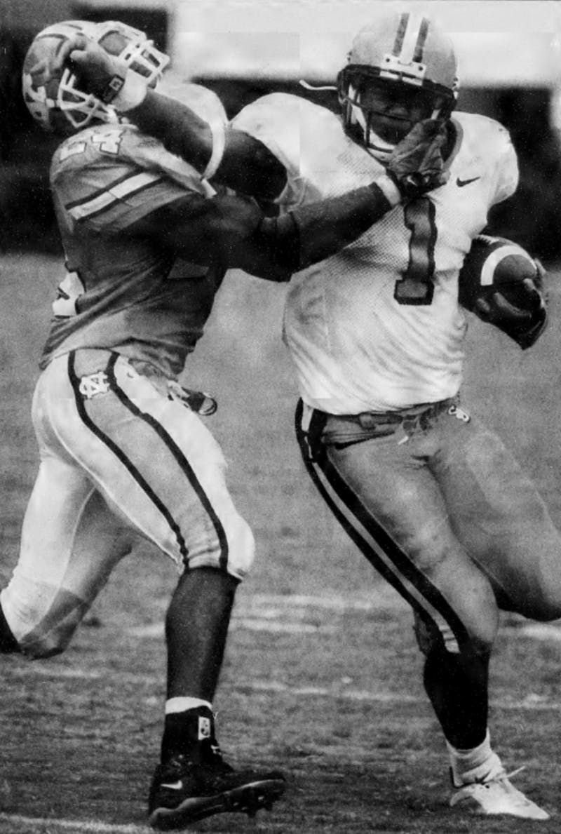 DTH Archive. Syracuse running back Damien Rhodes (1) fights off UNC safety Dexter Reid in the Orangemen's triple-overtime win. Syracuse overcame a 17-point third quarter deficit to tie the game on a field goal. Photo by Kimberly Craven.
