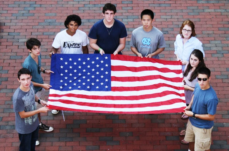 Ivan Pogrebnyak, Peter Vance, Kieran Preissler, Ian Helfrich, James Ding, Courtney Bruun-Andersen, Samantha Halle and Jose Labra Escudero pose with a flag. Learn about their stories online.