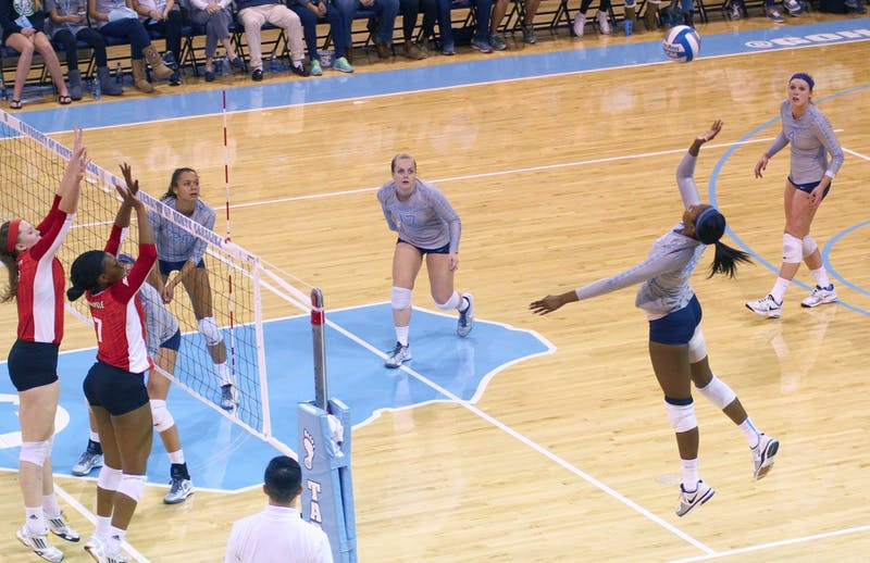 Taylor Leath (43) spikes the ball over the net against Louisville Friday night.