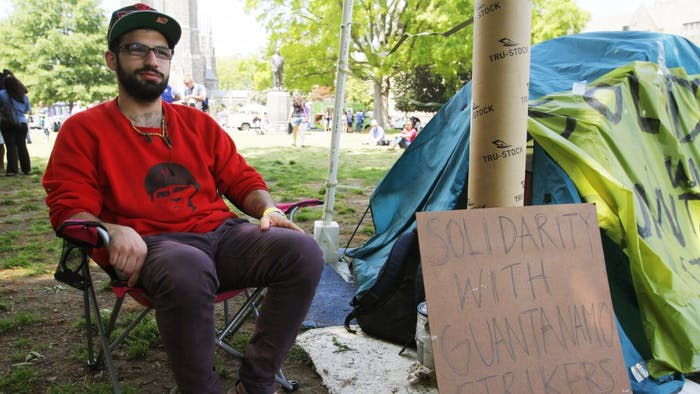 """Ahmad Jitan, a senior at Duke, sits beside the tent that students from UNC and Duke have been camping out in on Duke's campus. The group of students is standing in solidarity with the prisoners on hunger strike at Guantanamo Bay. """"What is something that we could do?"""" Jitan said he thought before deciding to camp out. The group has a petition you can sign that calls for the closing of Guantanamo Bay. Jitan was sitting in the quad on LDOC, surrounded by food trucks and students getting ready for the evening's concerts.The group will be camped out indefinitely."""