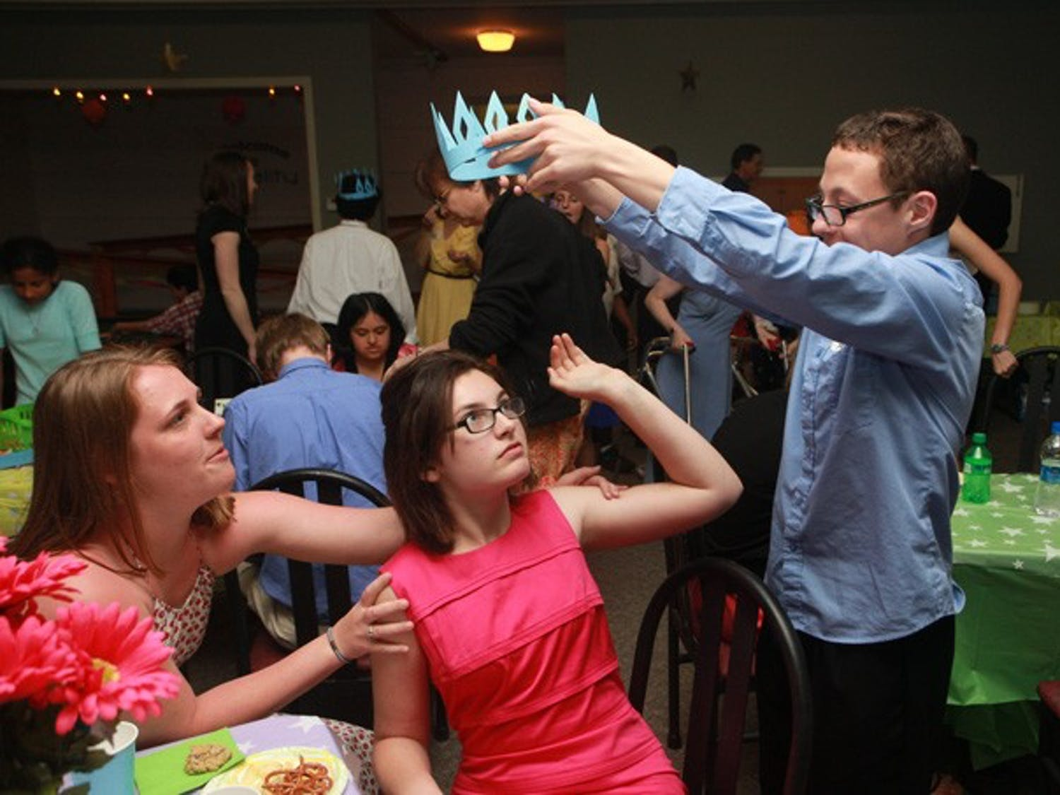 While taking a break from the festivities, Aaron attempts to crown his date, Zoe.