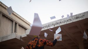 DTH Photo Illustration. A student throws test materials in the air. UNC, along with other universities, waived their SAT requirement for admissions, providing relief to many applicants.