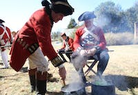 """Revolutionary War reenactment as part of Twelfth Annual Revolutionary War Living History Day in Hillsborough Saturday 2-22-14. Reenactment of His Majesty's 64th regiment of foot during the year of 1781. Right-  Mark Dappert is from Charlotte, reenacting a Sgt., been reenacting for 25 years. Here he is cooking """"spotted dog,"""" salt pork and cabbage.Left- David Snyder is from Efland, reenacting a Captain of Infantry, been reenacting since 1976 and started because of the bicentennial. He has an interest in American history and wanted to learn more about the British side of the story."""
