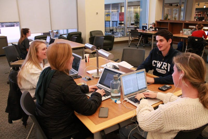 From left to right: Lauren Atkinson, Grace Clarke, Lauren Chamblee, and Sam White talk about homework together in Davis Library.