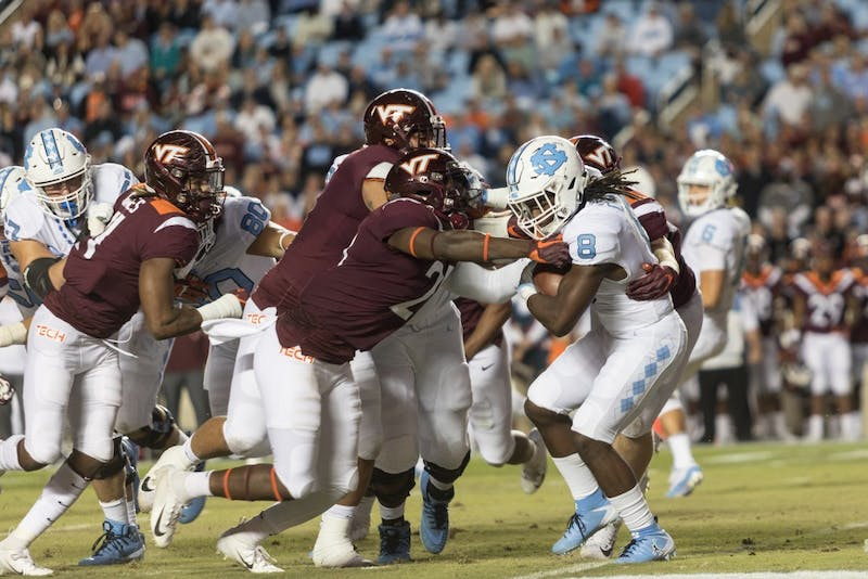 Sophomore running back Michael Carter (8) battles a swarm of defensive players during the Tar Heels' 22-19 loss against Virginia Tech on the night of Saturday, October 13, 2018 in Keenan Memorial Stadium in Chapel Hill, NC.