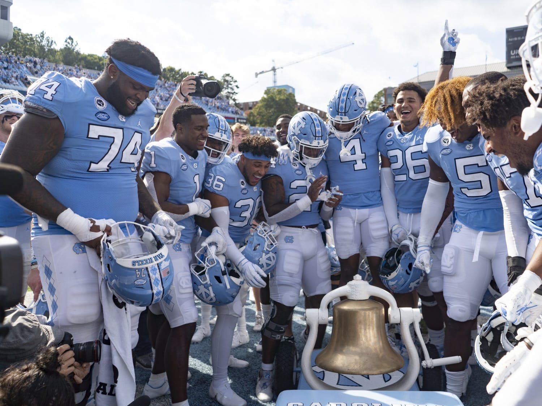Carolina football teammates ring the Victory Bell after defeating Duke 38-7 in Kenan Memorial Stadium on Oct. 2, 2021.