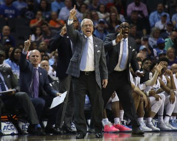 UNC head coach Roy Williams raises his hand during the first half against Louisville in the ACC Tournament quarterfinals at the Spectrum Center in Charlotte.