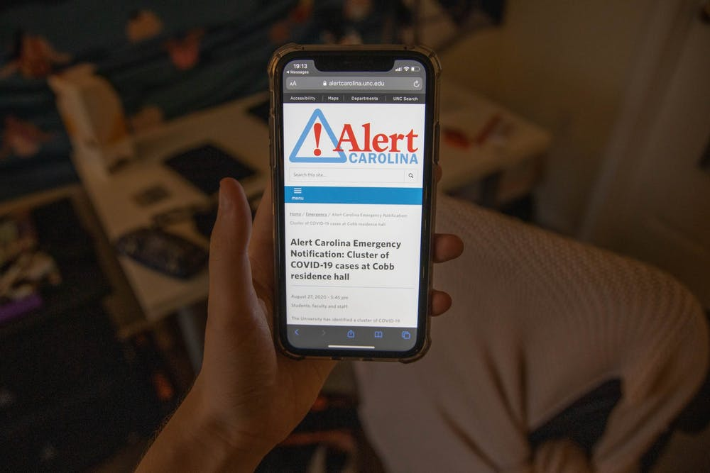 <p>DTH Photo Illustration. A student looks at the latest Alert Carolina notification about a cluster at Cobb Resident Hall. The university will no longer send Alert Carolina notifications about clusters on campus, UNC announced on Friday, Aug. 28, 2020.</p>