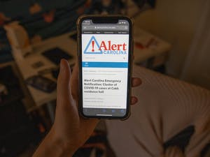 DTH Photo Illustration. A student looks at the latest Alert Carolina notification about a cluster at Cobb Resident Hall. The university will no longer send Alert Carolina notifications about clusters on campus, UNC announced on Friday, Aug. 28, 2020.
