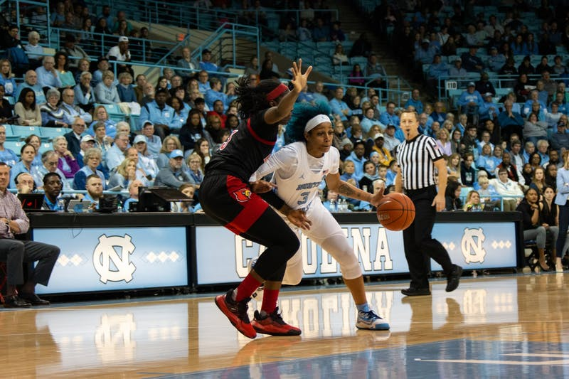 Senior redshirt guard Madinah Muhammad (3) dribbles the ball past an opposing player in the game against Louisville at Carmichael Arena on Sunday, Jan. 19, 2020. UNC lost 67-74.