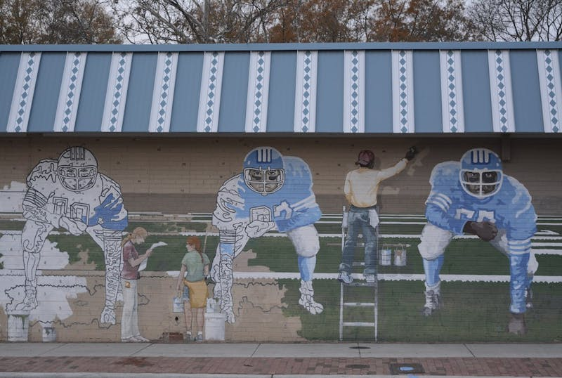 The paint-by-number mural features UNC football players and is located on the side of Pantana Bob's.