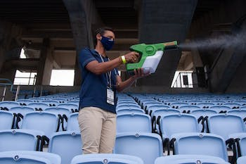 UNC athletic facilities worker Jaci Field disinfects the seats in Kenan Memorial Stadium after a football game against Syracuse on Saturday, Sept. 12, 2020.