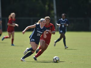 UNC Sophomore Forward Alessia Russo (19) dribbles past Louisville Senior Defender Gabrielle Vincent (14) during  Saturday's game against Louisville at WakeMed Soccer Park. UNC won 5-1