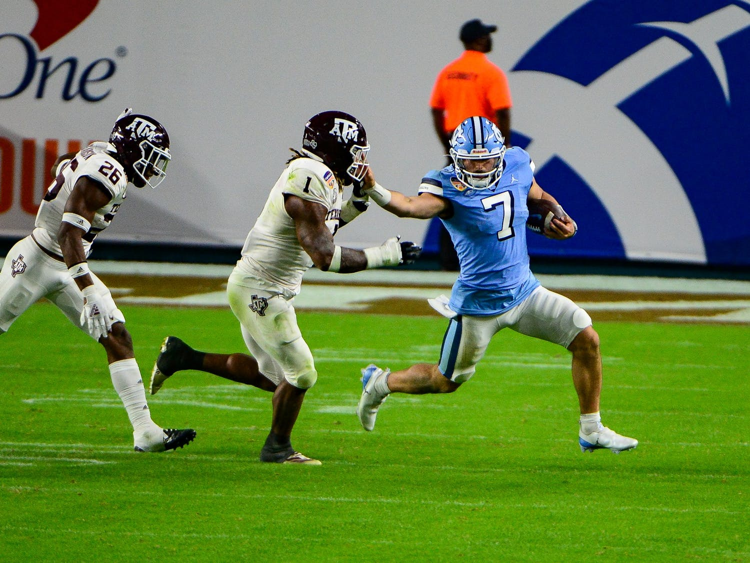 UNC sophomore quarterback Sam Howell (7) attempts to keep Texas A&M's senior linebacker Buddy Johnson (1) away during the Capital One Orange Bowl in Hard Rock Stadium on Saturday, Jan. 2, 2021. Texas A&M beat UNC 41-27.