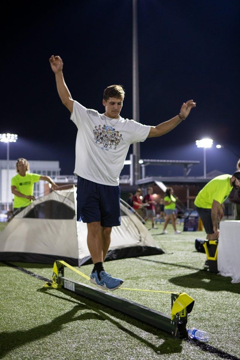 Luke Eggleston, a junior economics major, balances on the slack line during Fallfest on Hooker Fields on the evening of Sunday, August 18 2019.