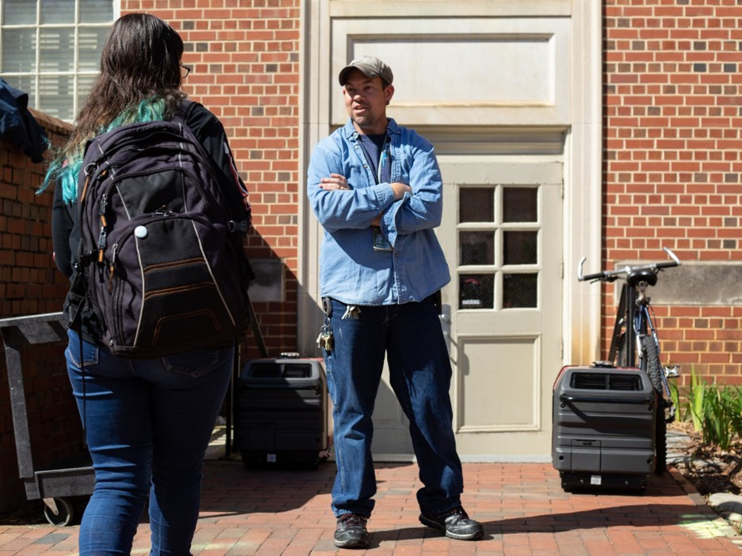 "Tim Holsonback, a maintenance worker at UNC, informs student Abby Gancz that Phillips Hall is closed on April 3, 2019. ""The only thing that I know happened was that they had a water main break in there this morning and it knocked all the electrical out, and there's been a flood on the first floor and the basement,"" Holosonback said. ""We're dealing with it the best we can because we got to get the water out of the building before we can get the electricity back up."""