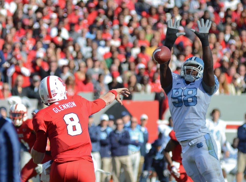 """<p><span class=""""caps"""">UNC</span> defensive end Donte Paige-Moss attempts to block NC State quaterback Mike Glennon&#8217;s pass in <span class=""""caps"""">UNC</span>&#8217;s 13-0 loss to NC State at Carter-Finley Stadium in Raleigh, NC. </p>"""