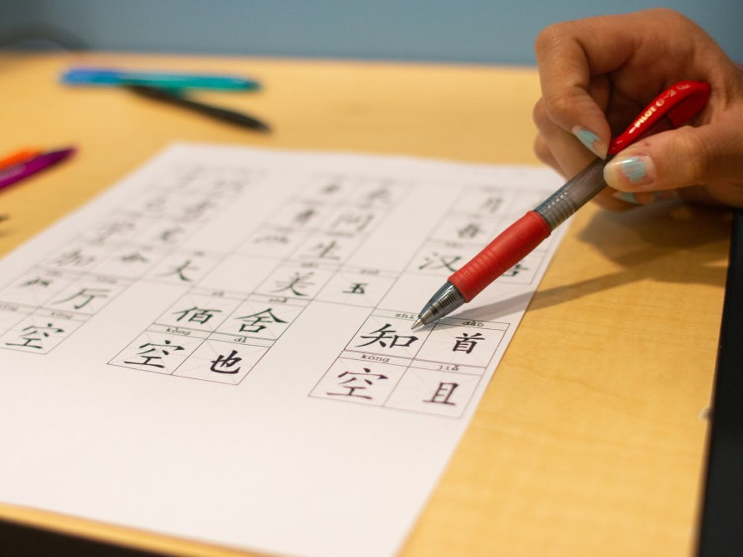 DTH Photo Illustration. A student points at Mandarin script on a practice worksheet in Chapel Hill, N.C., on Monday, March 18, 2019. Glenwood Elementary resolved to expand their Mandarin immersion program and phase out other tracks, prompting redistricting for current kindergarteners whose parents did not want them to participate.