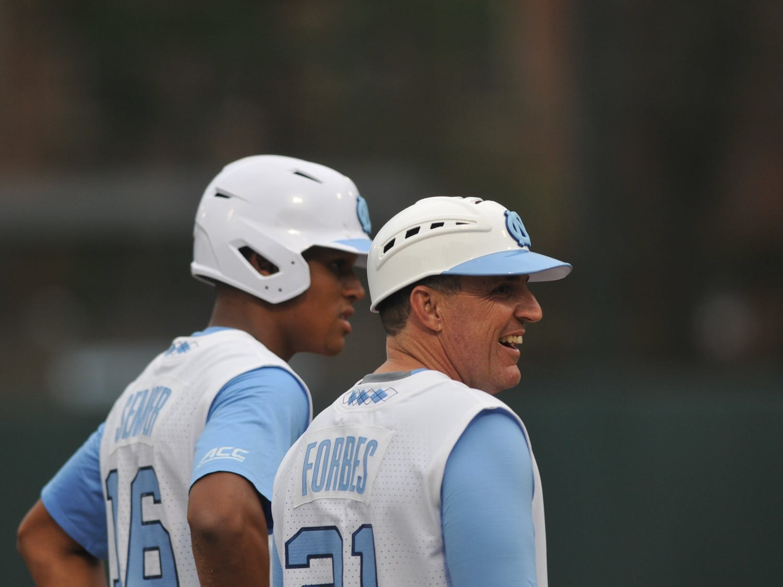 Earl Semper (16) talks to new baseball head coach Scott Forbes while waiting on third base on Tuesday, Feb. 25, 2020 in Boshamer Stadium against NC A&T. UNC beat NC A&T 8-0.