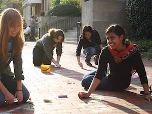 Sophomore business major Jess Hetzel (left) and sophomore international studies major Mitali Dayal participate in Chalking Sidewalks.
