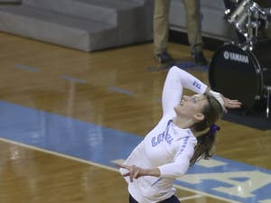 Junior Taylor Fricano (5) goes up for a serve Friday night against UVA.